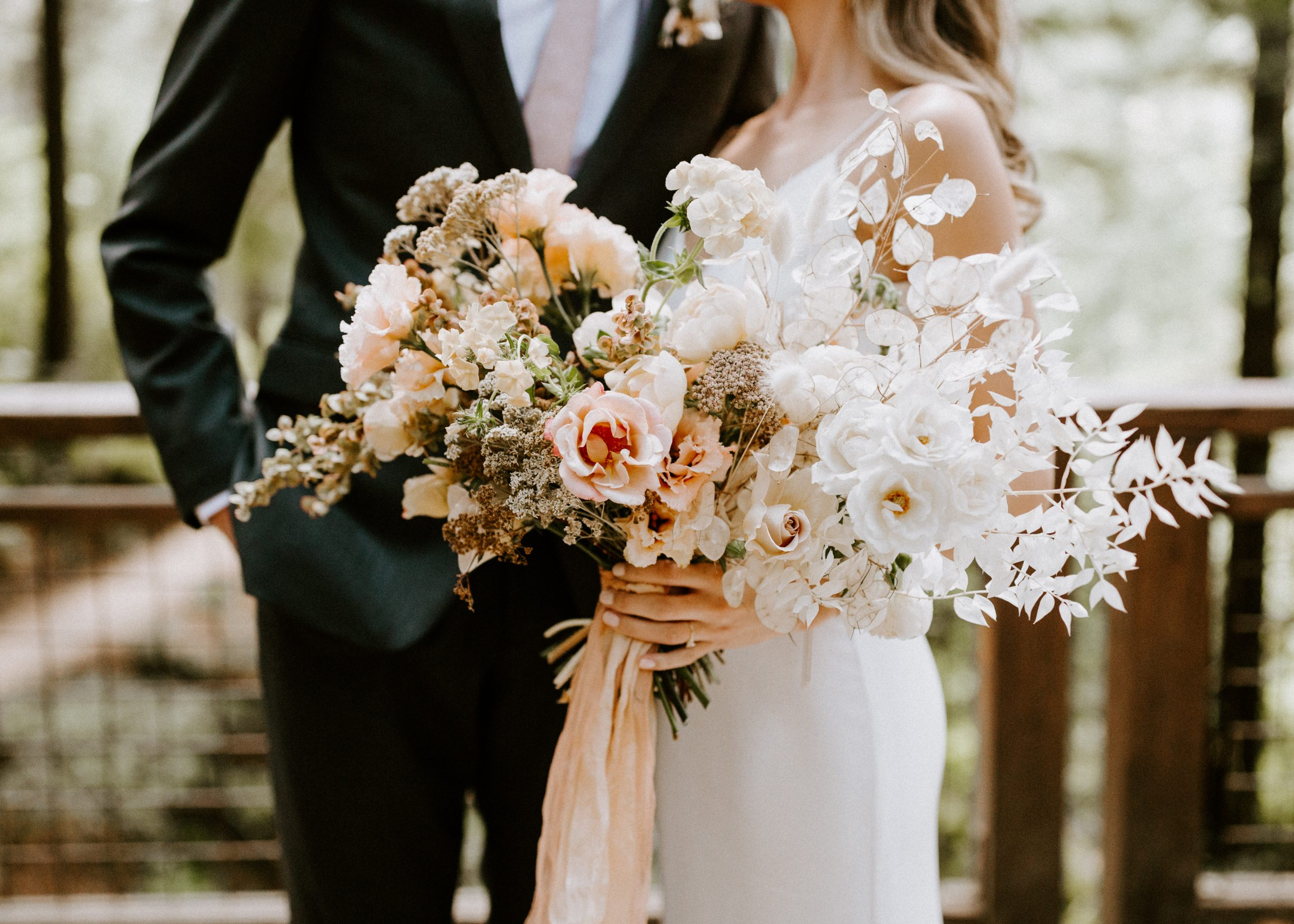 Bride holding a modern style bouquet with blush and white blooms and hanging silk ribbon