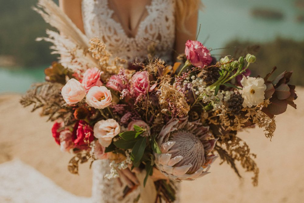 Bride holding a boho bouquet with funky blooms and dried elements.