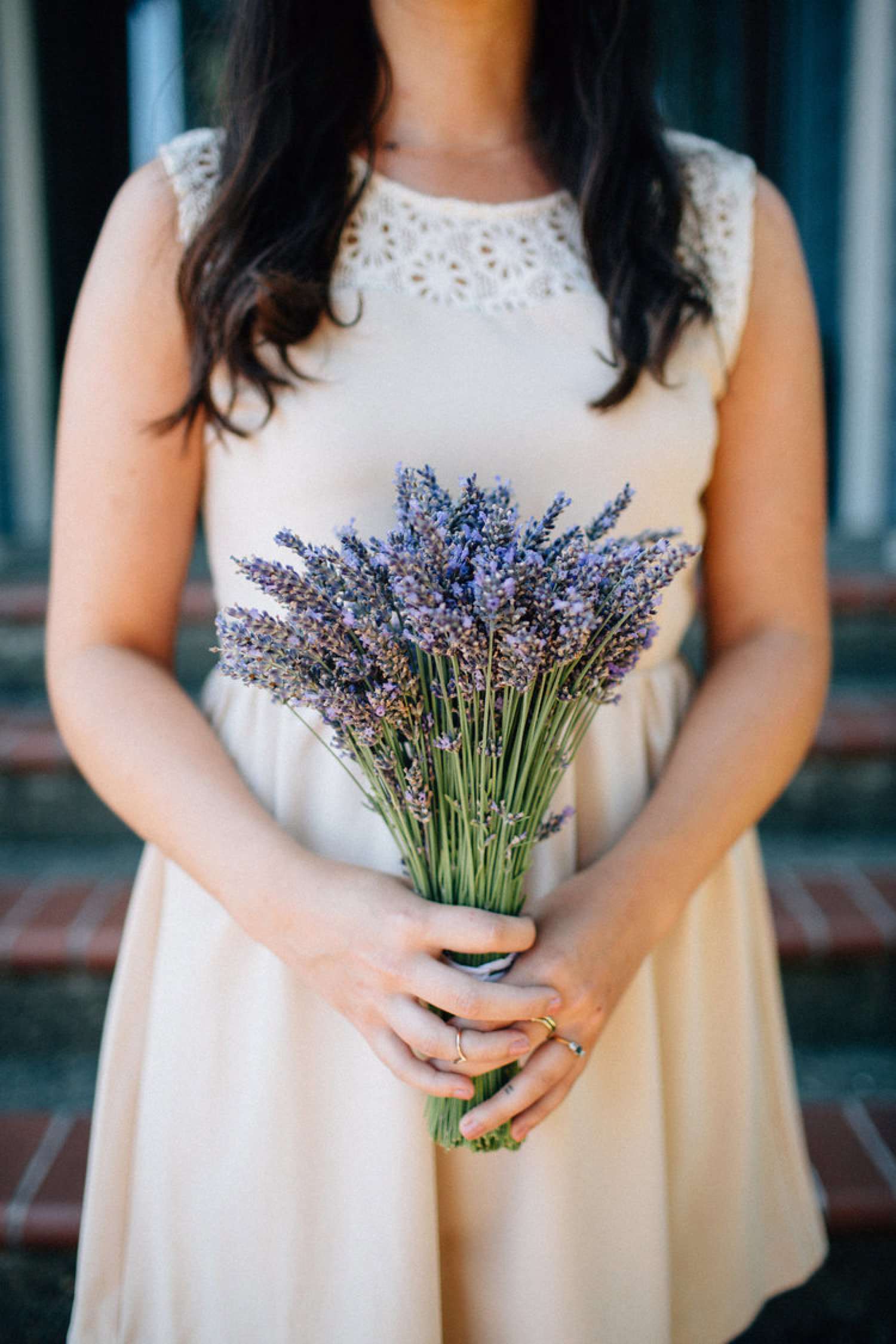 Bride holding a rustic bouquet of lavender.
