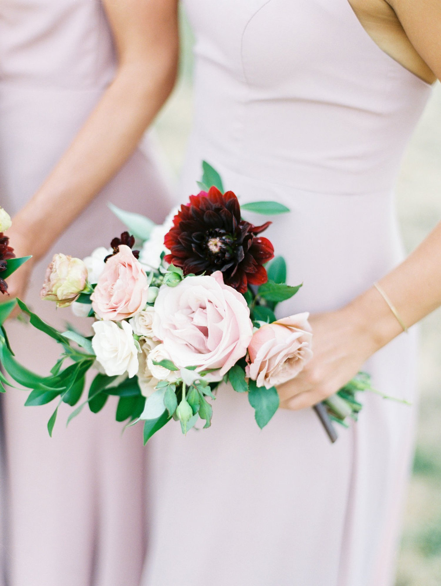 photo of a bridesmaid holding bouquet of blush and burgundy roses and dahlias