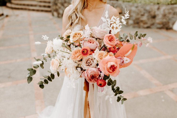 photo of a bride holding a bouquet with blush and coral roses