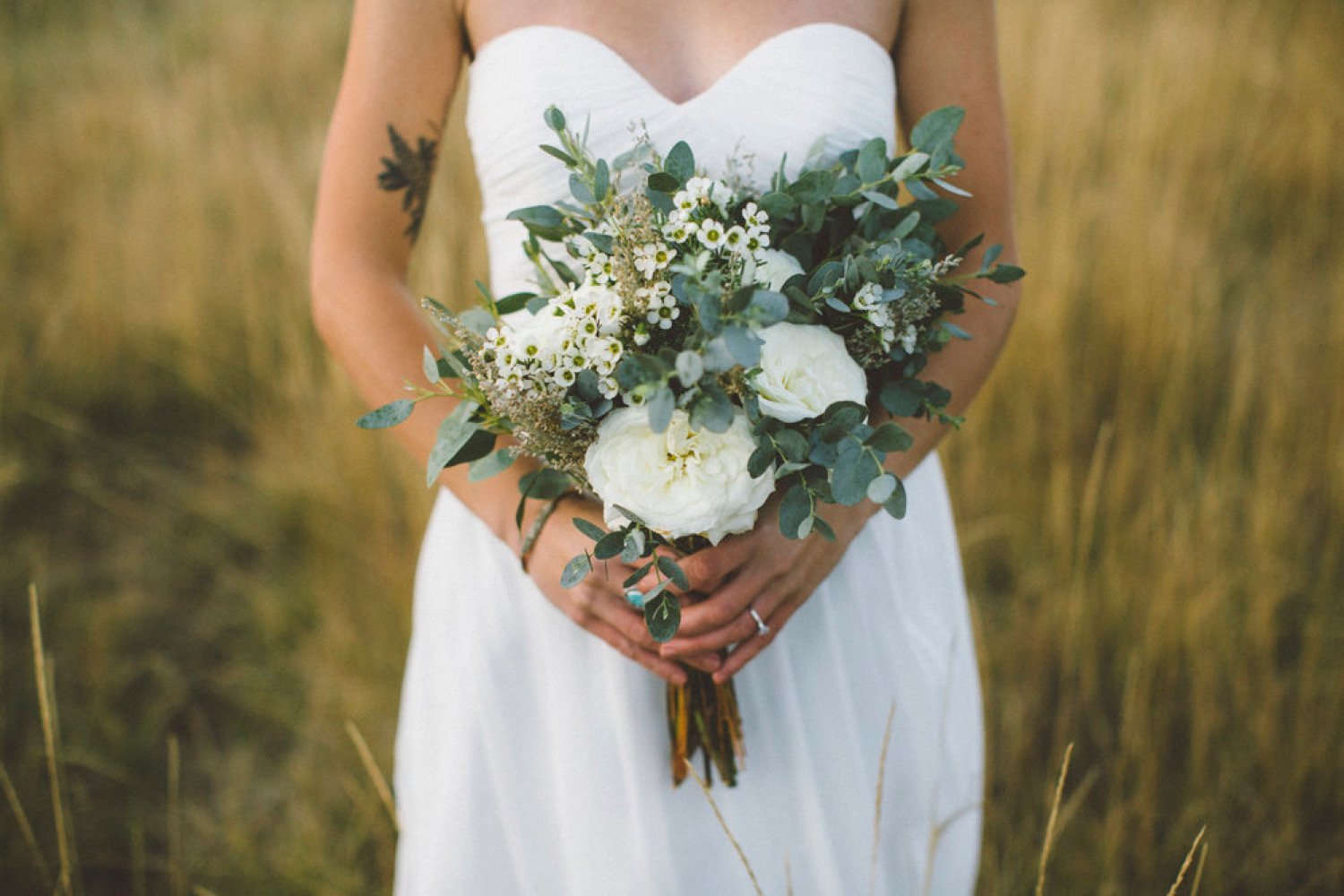 photo of a bride holding a bouquet of white roses and greenery
