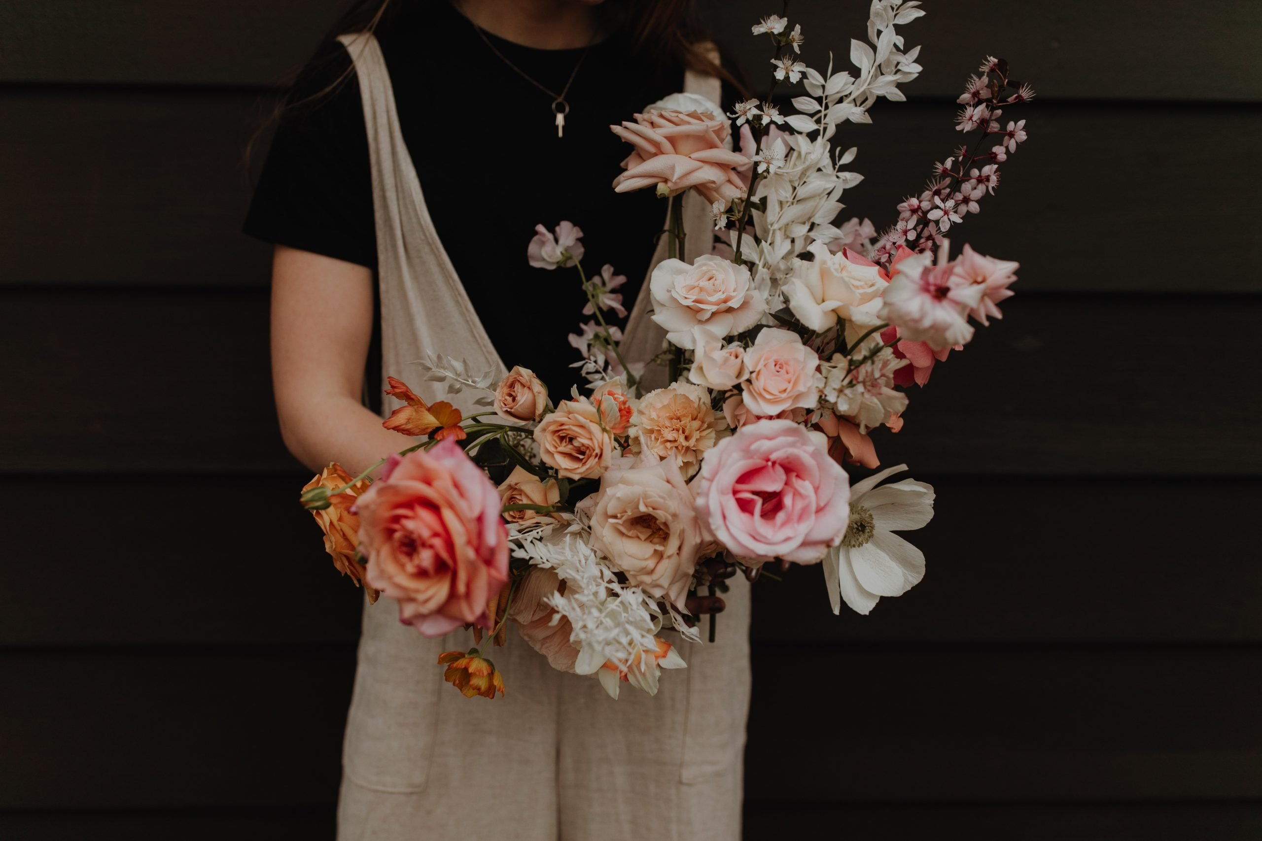photo of Good Seed florist holding a romantic bouquet with peach and blush tones.