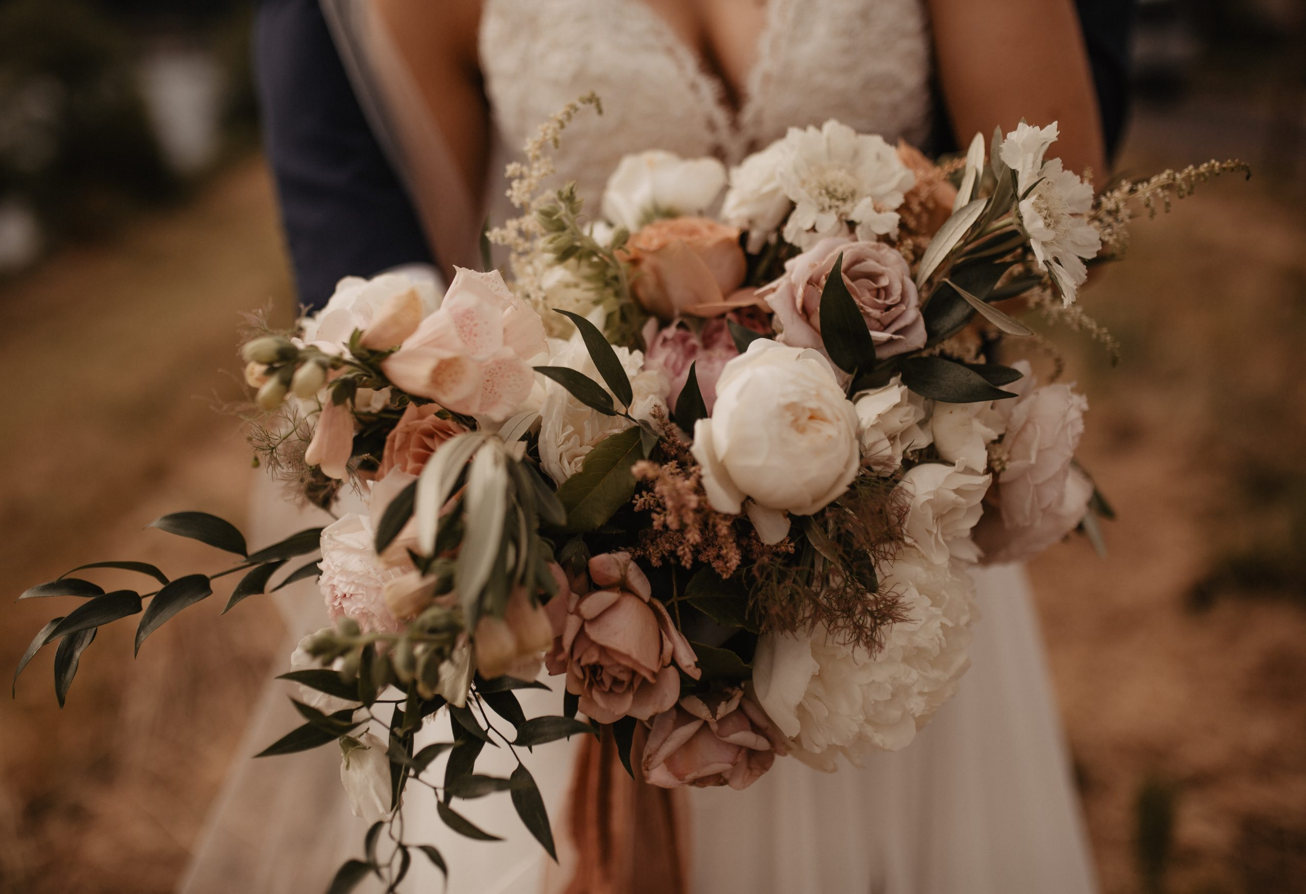 Bride holding a moody bouquet with neutral flowers and greenery