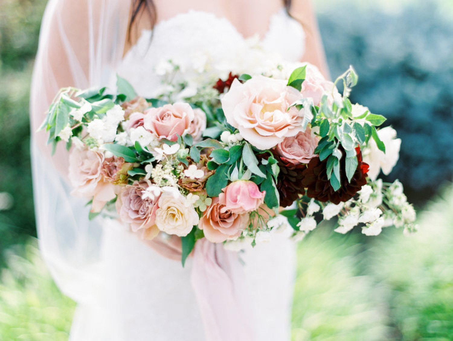 Bride holding a classic bouquet with blush and burgundy tones and greenery.