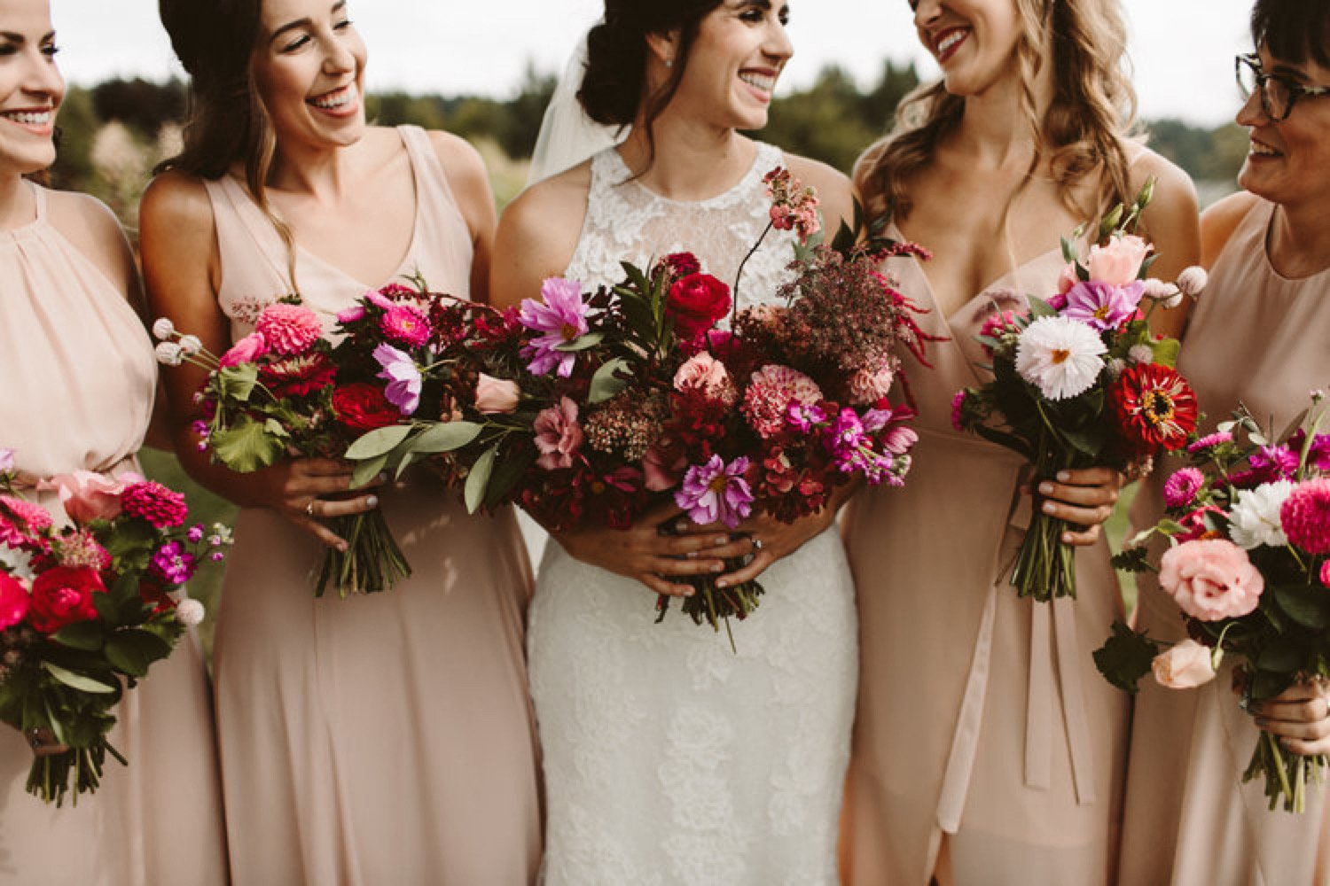 Bride and her bridesmaids holding whimsical bouquets of hot pink and purples.