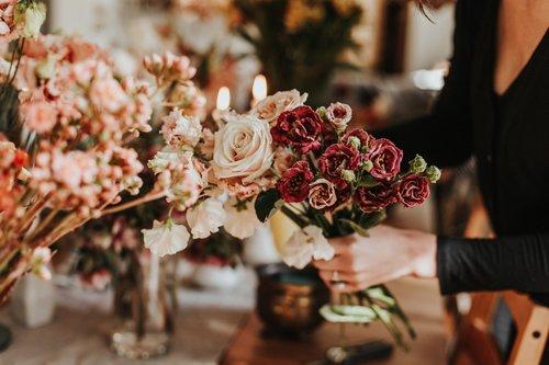 austin florist arranging a bouquet of blush and burgundy blooms