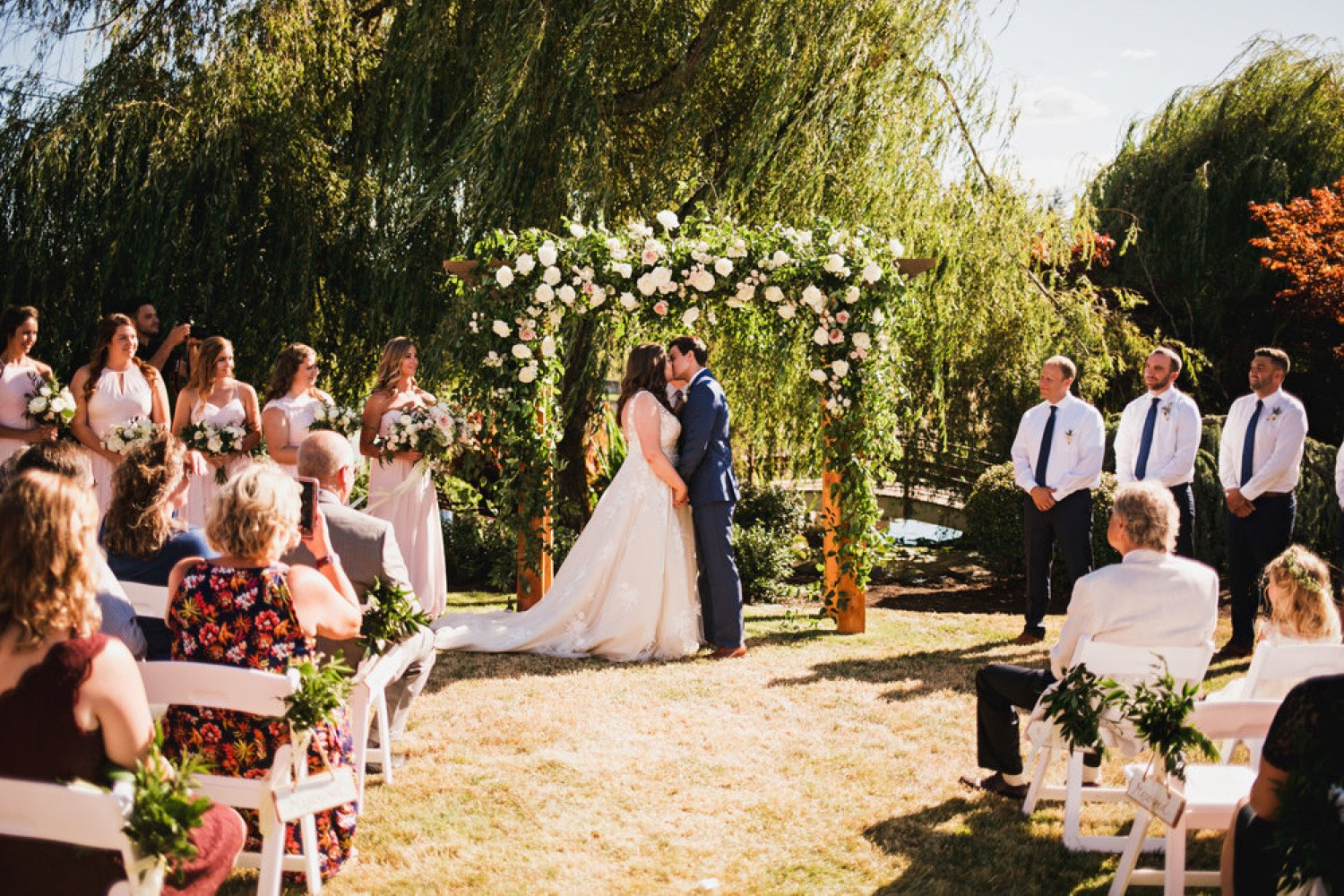 couple getting married in front of an arbor decorated with greenery and floral