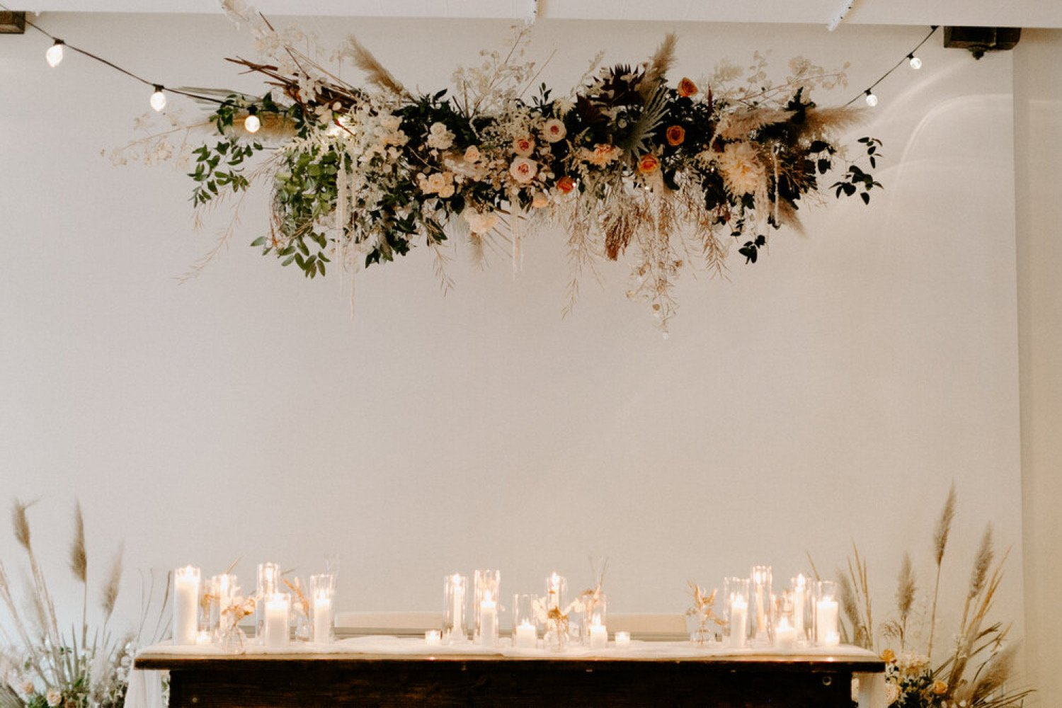 large floral installation hanging from the ceiling over a wedding reception table