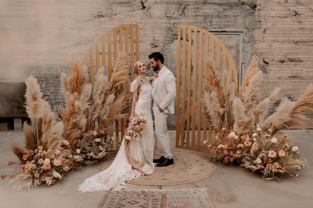 couple standing in front of a boho inspired ceremony floral installation with pampas grass and floral
