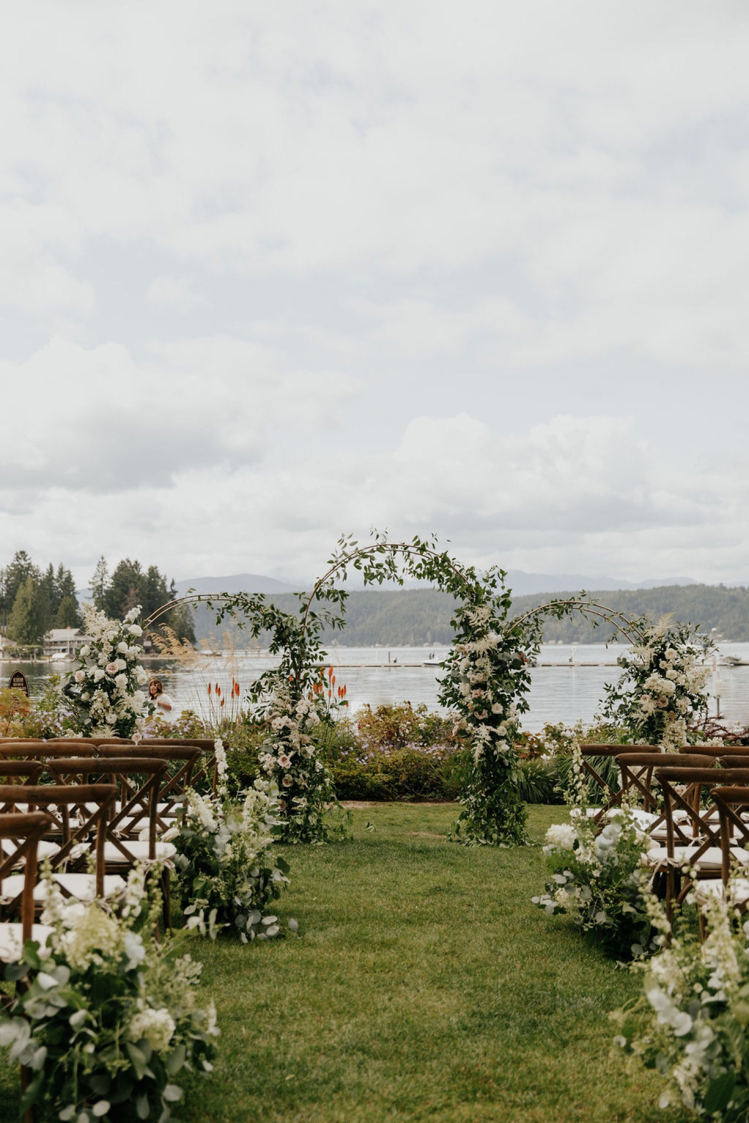 three circle arbors decorated with floral and greenery for a wedding ceremony on a lake.
