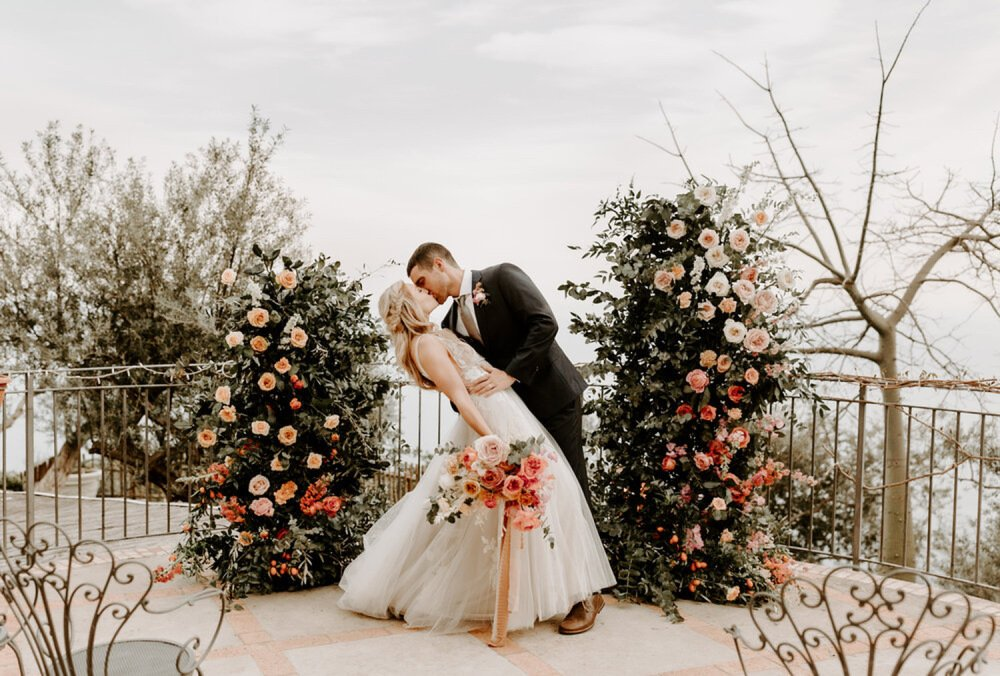 bride and groom kissing in front of lush floral ceremony arch