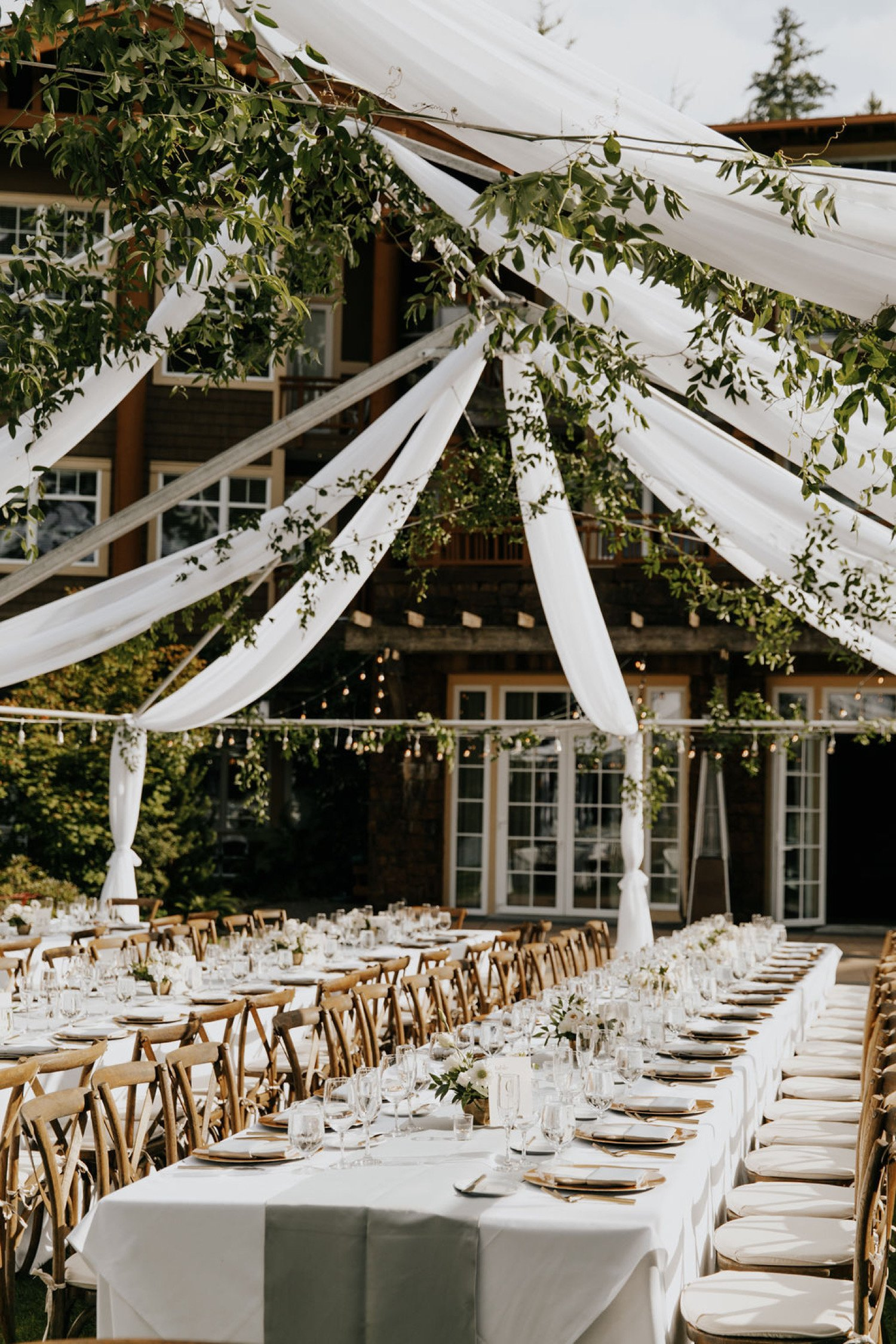 Wedding reception set up with long farm tables, hanging drapes and hanging greenery