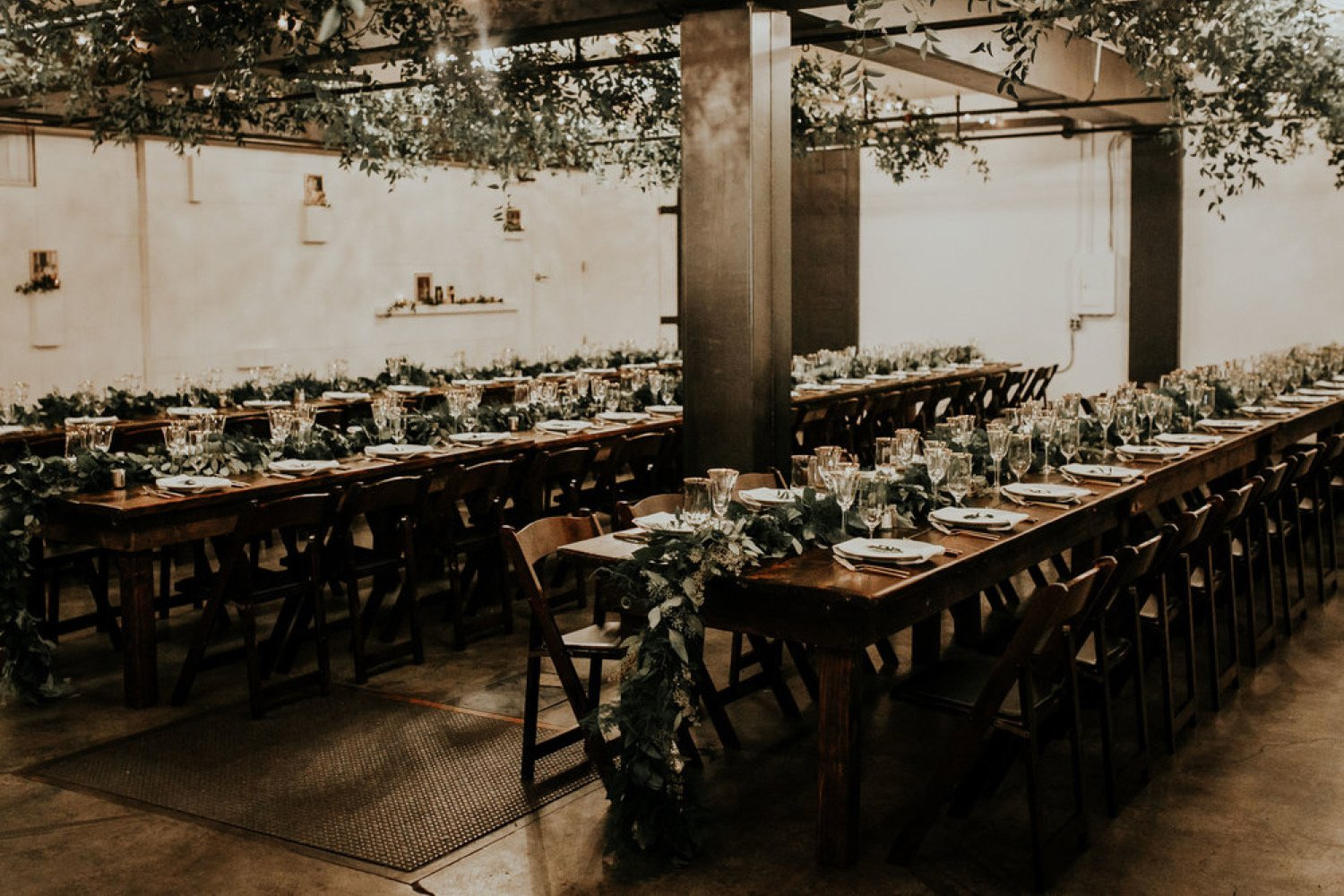 Long farm tables at a wedding reception with long greenery garlands