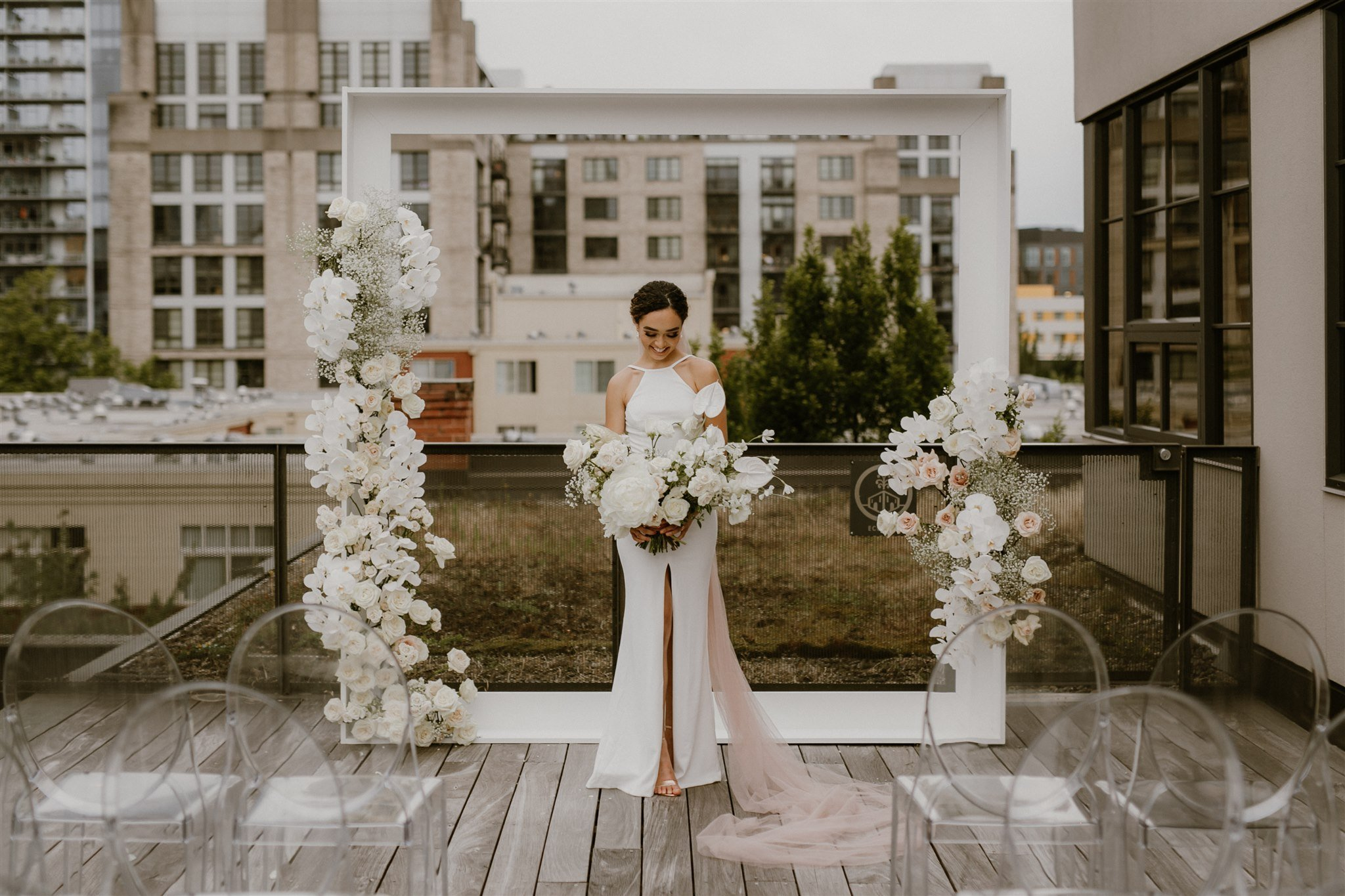 bride holding a lush white bouquet, standing in front of a floral ceremony arch on a rooftop