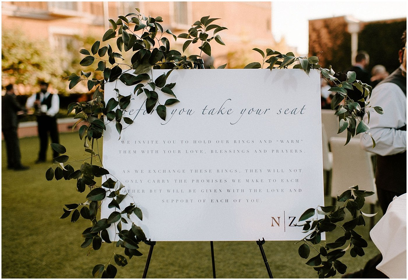 wedding sign decorated with airy greenery