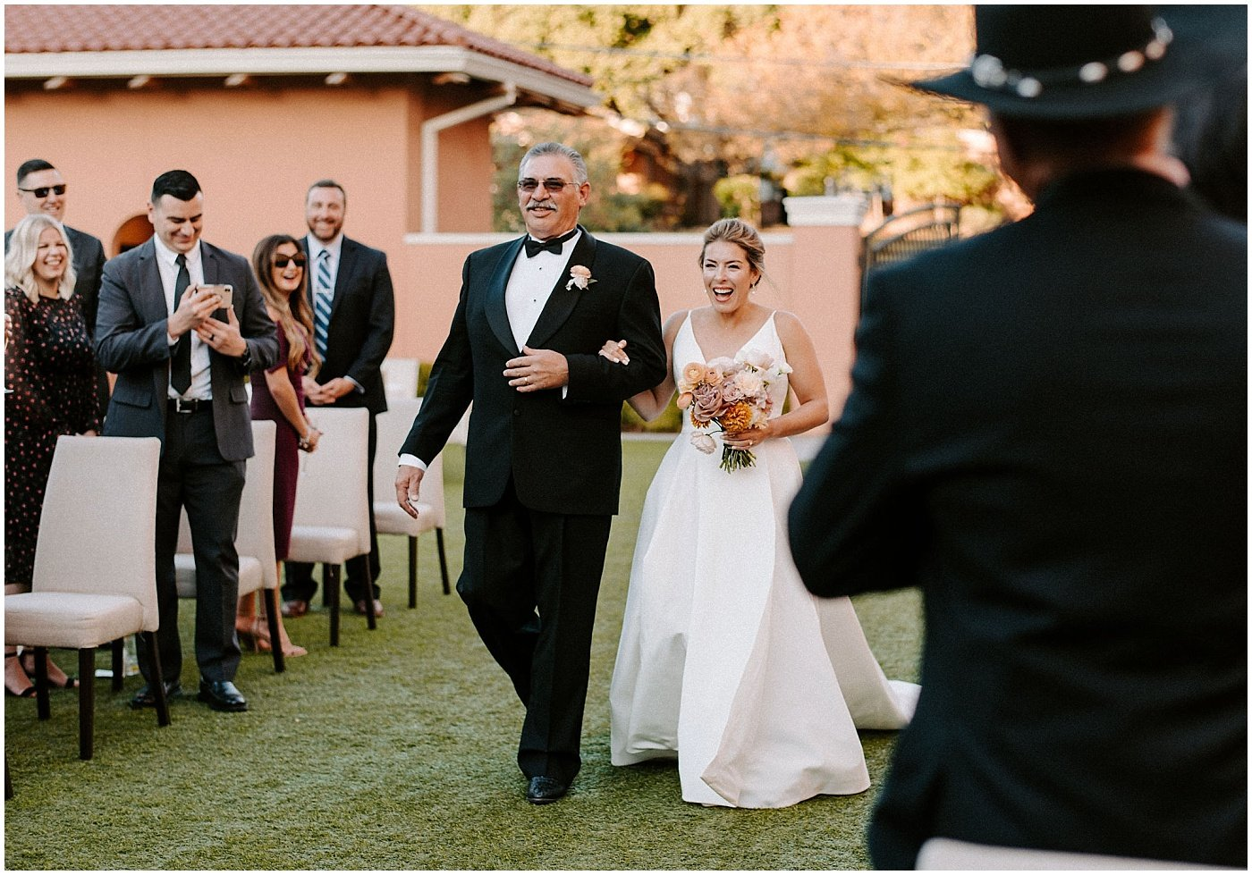 father and bride walking down the aisle