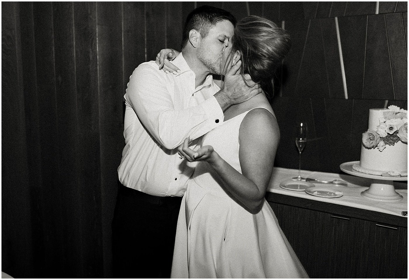 bride and groom kiss after cutting their cake