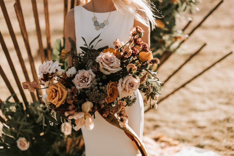 bride holding a large wedding flower bouquet of golden roses and hanging silk ribbon.