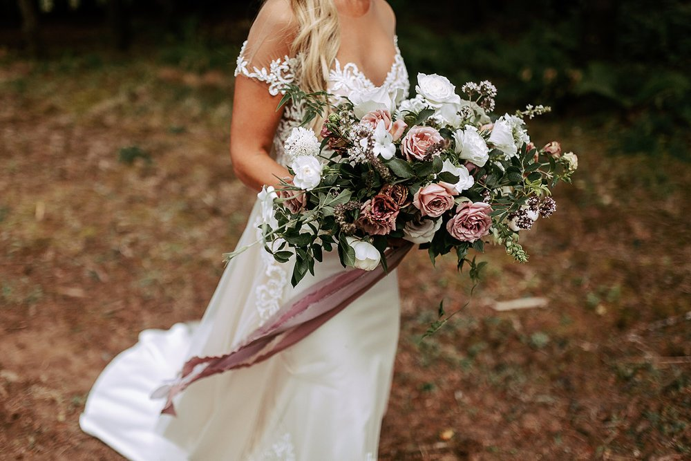 a bride holding a lush wedding flower bouquet of white and blush roses and greenery, with trailing silk ribbon.
