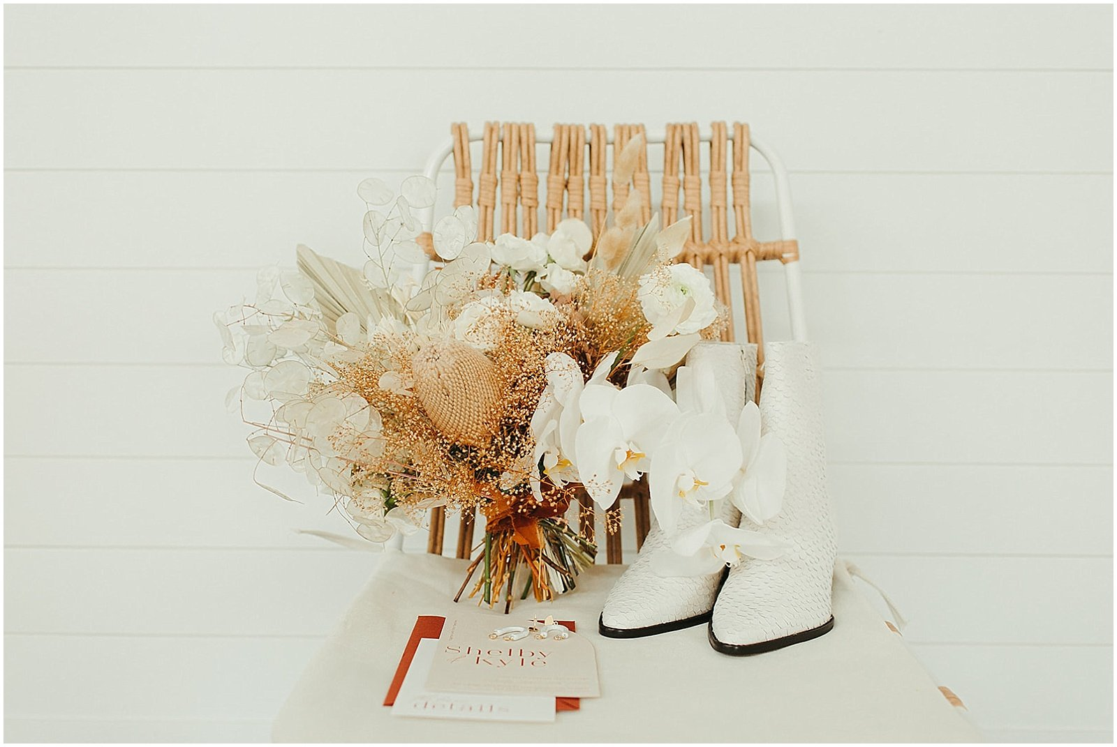 dried bridal bouquet with neutral, white and tan florals, next to brides white boots