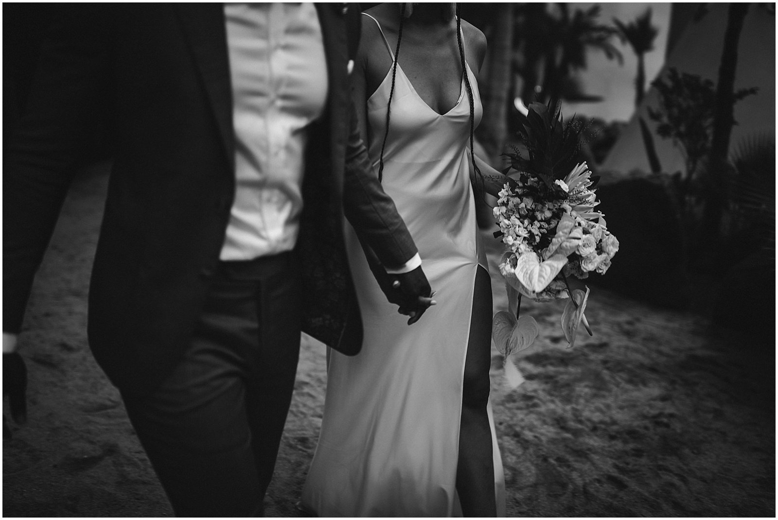 Bride and groom walking along the beach at Pachamama Resort in Todos Santos, Mexico