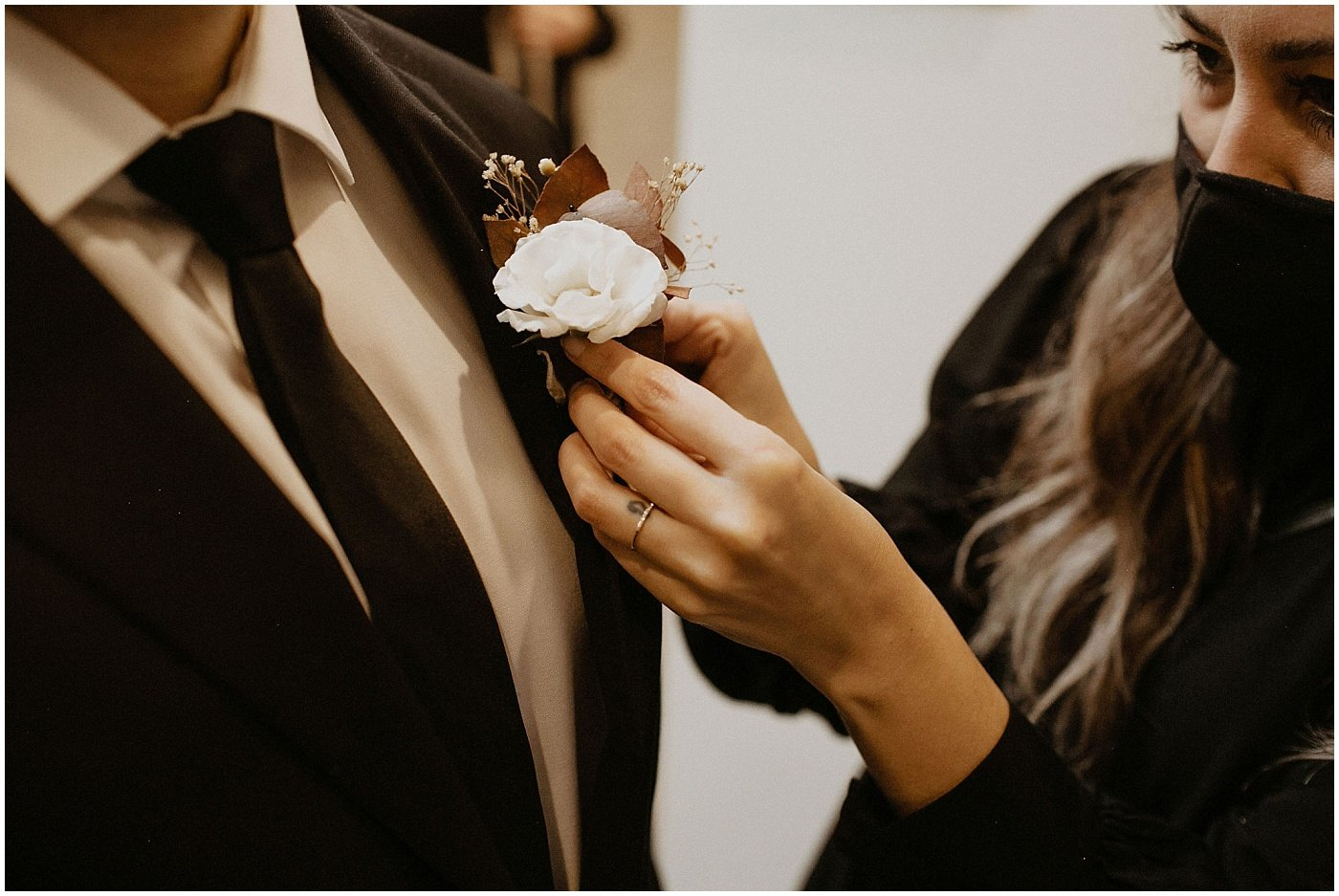 florist putting on groom's boutonniere
