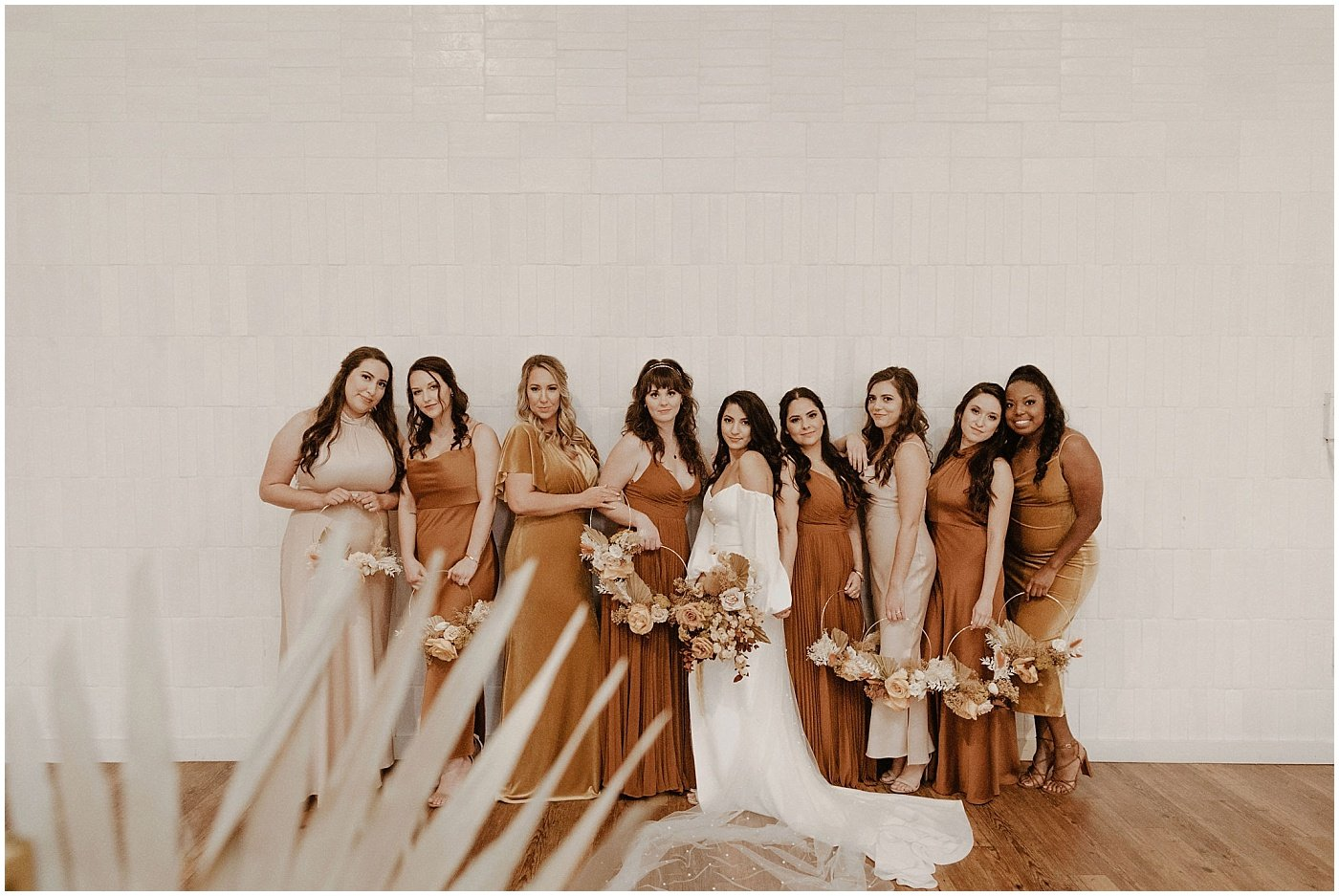 Bridesmaids wearing burnt orange long velvet dresses and holding hoops with florals