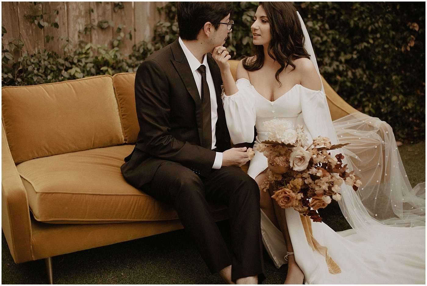 bride and groom sitting on a mustard couch, bride holding a boho bouquet with dried florals and roses