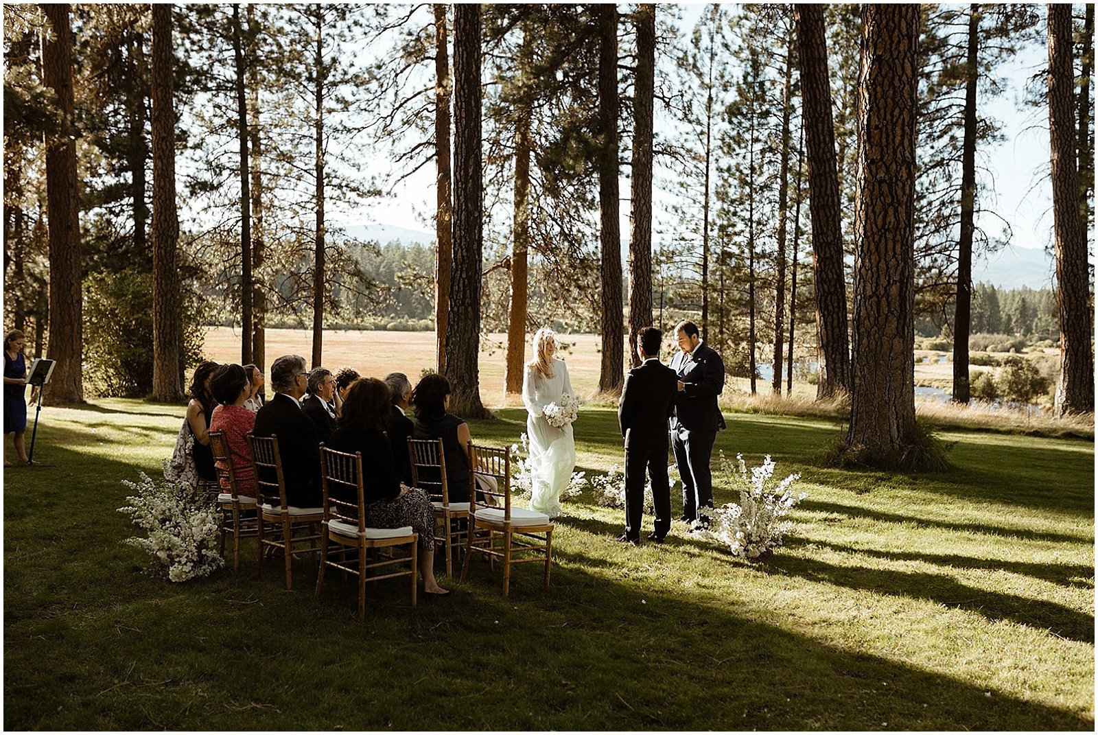 bride and groom exchanging vows, white and blush floral arrangements at ceremony location for an Oregon Wedding at House on Metolius
