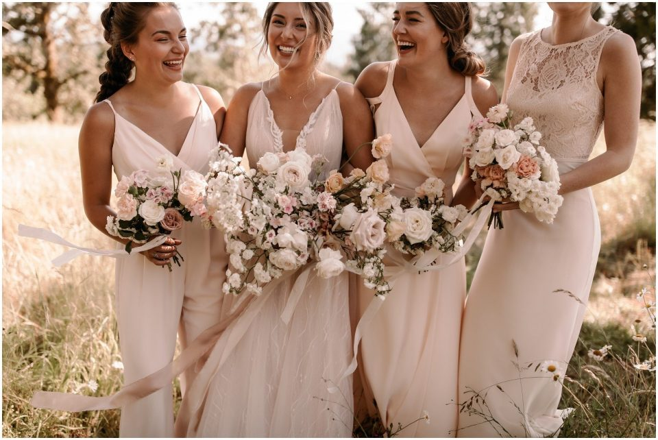 bride and bridesmaids wearing blush dresses and holding soft white and blush bouquets