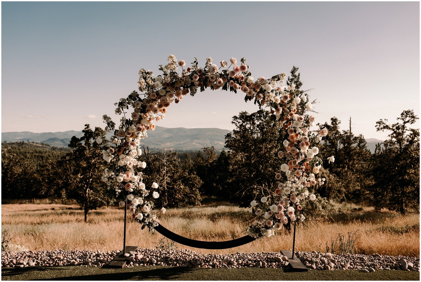 large circle ceremony arch covered in roses and greenery