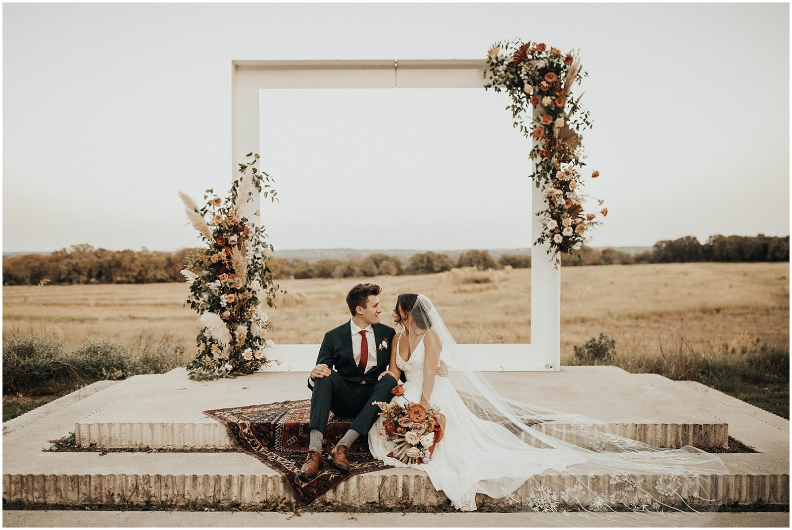 bride and groom sitting in front of ceremony floral arch
