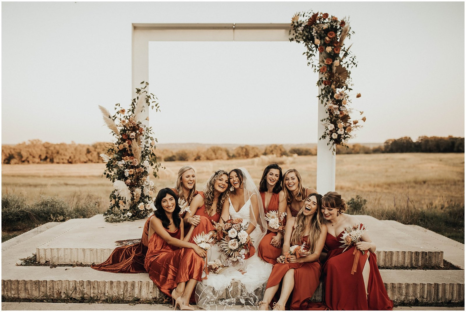 bridal party portraits, bridesmaids are wearing long rust colored dresses