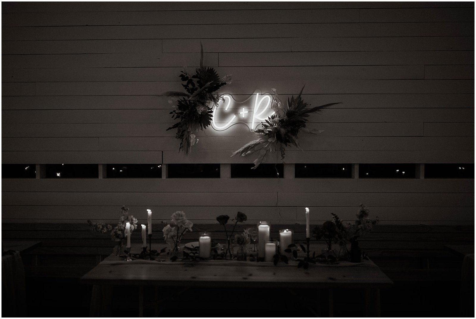 sweetheart table set up at wedding reception with neon sign