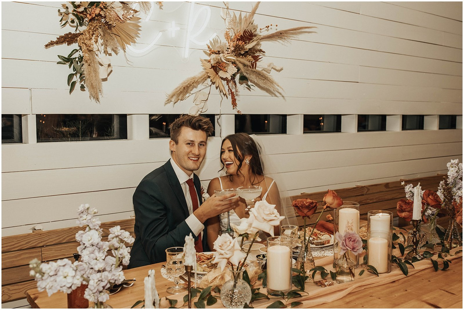 bride and groom sitting together at sweetheart table