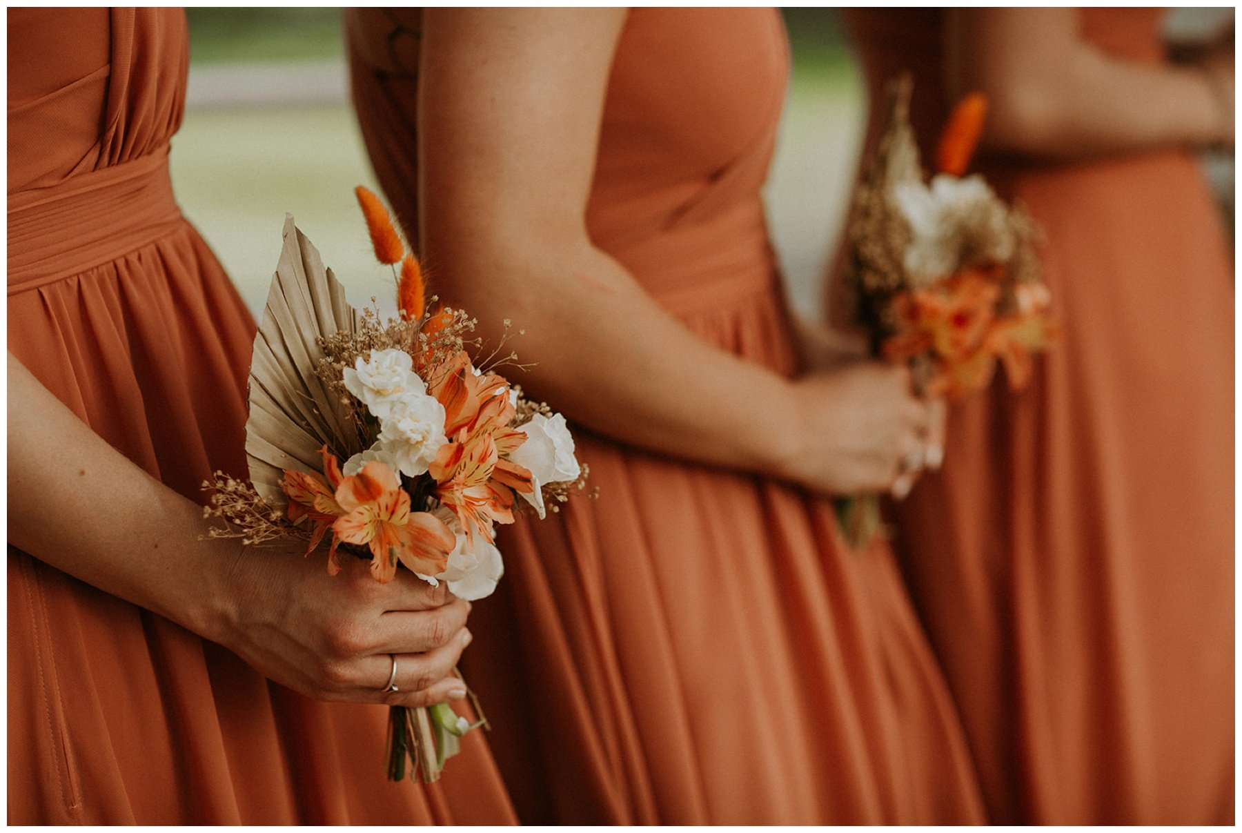 Bridesmaids wearing orange dresses and carrying bouquets