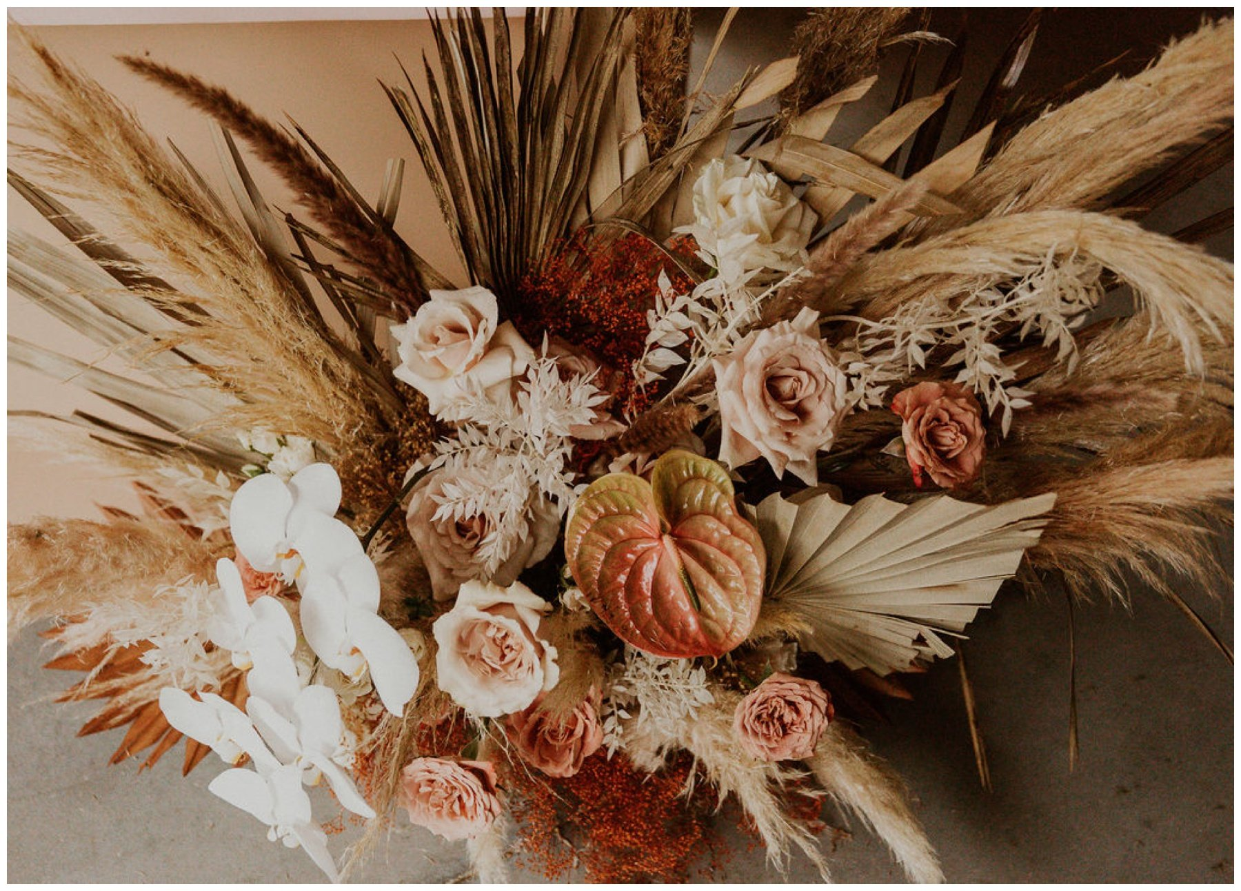 dried floral arrangement with pampas grass, blush roses, and orchids