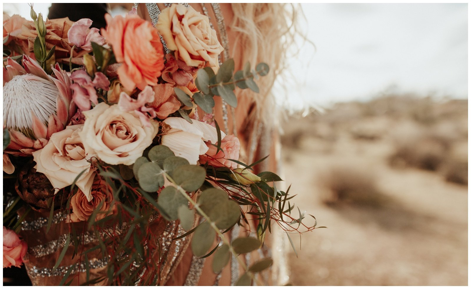 bride holding bridal bouquet with peach and pink flowers
