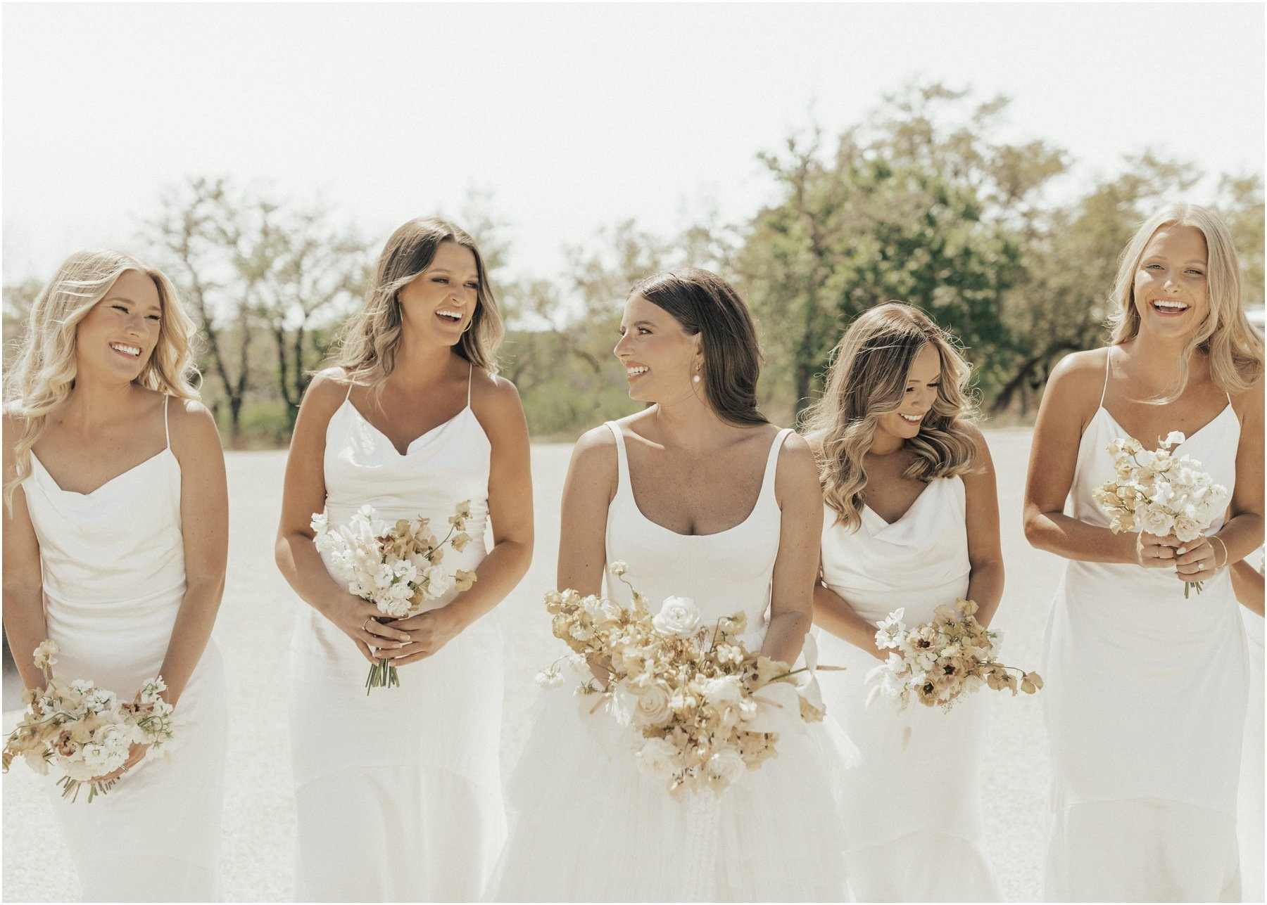 bride and bridesmaids holding modern bouquets with white flowers